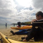 Resting after a hard paddle along the cornwall coast. The group have pulled the sea kayaks up onto the sandy beach and are sitting down together while staring out to sea. A lot to contemplate.