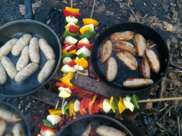Sausages sizzling in a pan and skewered veg cooking over the open fire