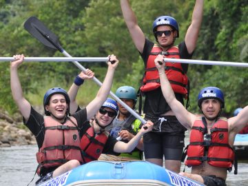The team celebrating successfully navigating the rapids in the rafts. They are grinning from ear to ear and holding their paddles up high.