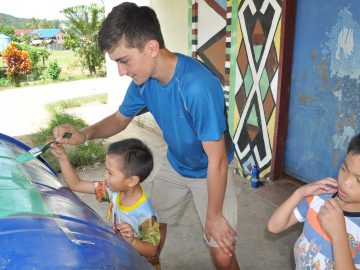 A little decoration being added to the water tank before it is installed. Two local children are helping George to paint.