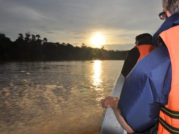 The sun is setting as the group make their way upriver in the little boat. The bright orange of the bouyancy aids is almost the same colour as the sun on the water.