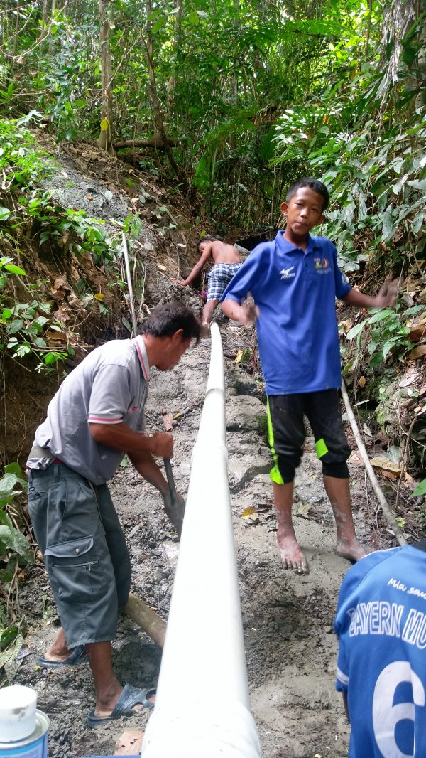 Setting out the pipeline for the flow of water into the village on a humanitarian aid expedition in Borneo