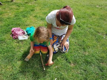 Child working with a parent to create a tent peg, using a variety of techniques to demonstrate safe knife use.
