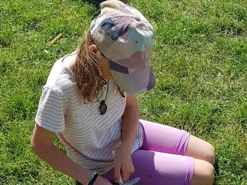 Young girl practising safe knife use while whittling a spatula from green wood.
