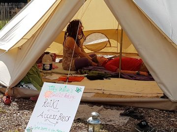 Reiki at the Wild Home Education Gathering. In a peaceful bell tent Tilly is working with a client to improve their health and well being.