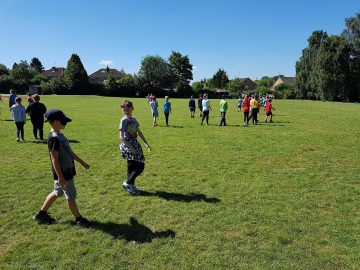 Children building trust and discovering how hard it is to walk in a perfectly straight line while blindfolded. In pairs, one child is blind folded, their task is to walk across the field in a straight line. Their partner is there to keep them safe but not to guide them. They are not managing to walk in a straight line!