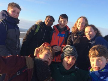 Eight smiling young people, all wrapped up in Arctic winter gear to keep themselves safe and warm. A brilliant blue arctic sky and a view over the frozen water of the river behind.
