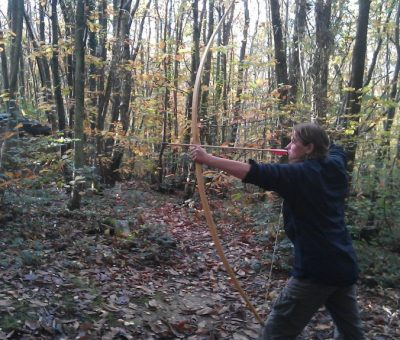 Hannah in the woods shooting a bow she made!