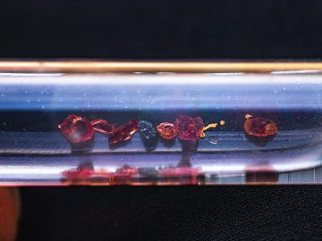 Gold garnet and megnetitie in a test tube or vile