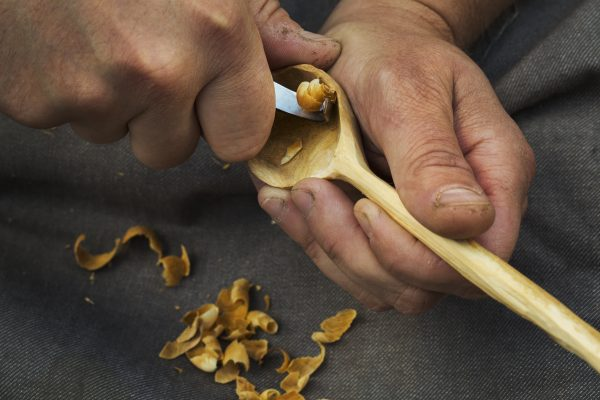 hand carving a spoon susing a crook knife