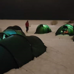 tents set up at night in the arctic to make a basecamp on the ice.