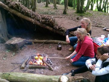 Students and young people sitting around a camp fire cooking food