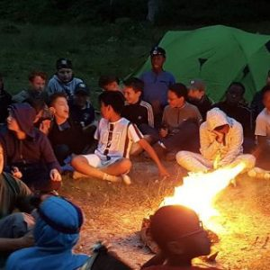 Group of school students and young people having fun around the campfire and camping with a tent in the background during the evening twilight . hero-1024x320_Polaris