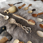 various spoons and kuksa on a reindeer skin made during carving classes