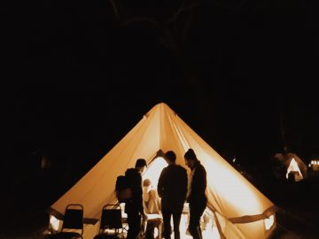 group of peole standing around a warmly lit tent in the dark